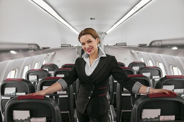 飛行機のジェット機の客室のスチュワーデス。モダンな飛行機のインテリア。笑顔のヨーロッパの女性は制服を着てカメラを見ています。民間商用航空。空の旅のコンセプト