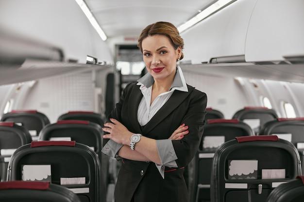 飛行機のジェット機の客室のスチュワーデス。モダンな飛行機のインテリア。腕を組んで笑顔のヨーロッパの女性は制服を着てカメラを見ています。民間商用航空。空の旅のコンセプト