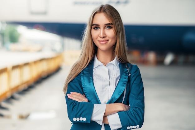 Стюардесса в униформе против здания аэропорта