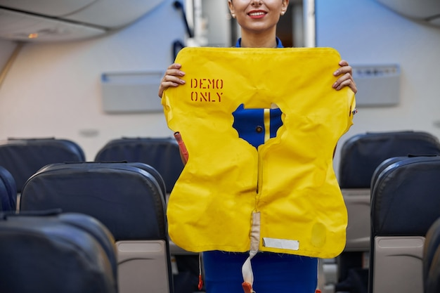 Stewardess is showing safety rules before fly at evening plane salon