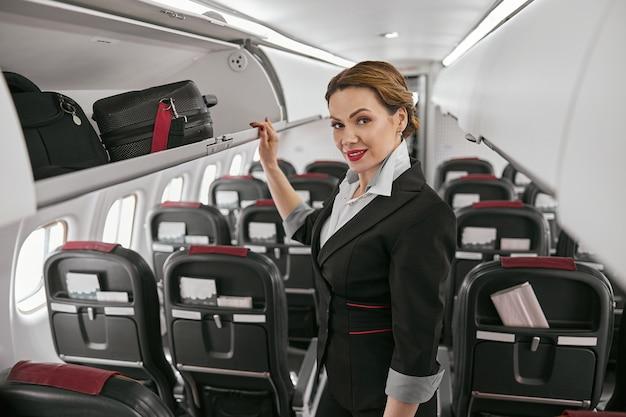飛行機のジェット機の客室の開いた棚の近くのスチュワーデス。モダンな飛行機のインテリア。笑顔のヨーロッパの女性は制服を着てカメラを見ています。民間商用航空。空の旅のコンセプト