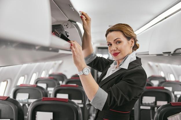飛行機のジェット機の客室のスチュワーデスオープニングシェルフ。モダンな飛行機のインテリア。笑顔のヨーロッパの女性は制服を着てカメラを見ています。民間商用航空。空の旅のコンセプト