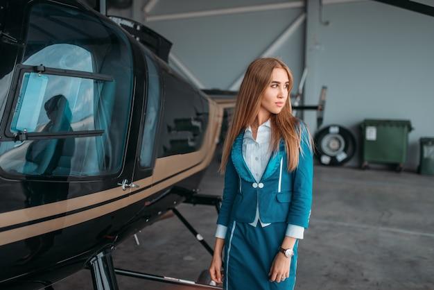 Стюардесса позирует против вертолета в ангаре