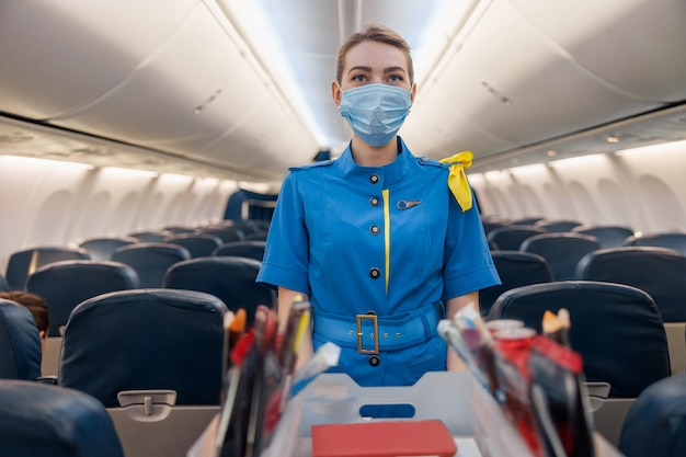 Stewardess in protective face mask and blue uniform serving food to passengers on aircraft. air hostess walking with trolley on aisle. travel, service, transportation, airplane concept