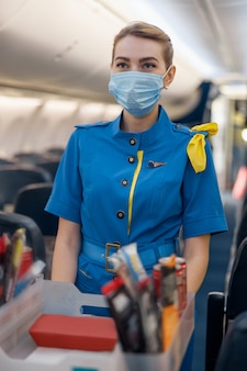 Stewardess in protective face mask looking away, serving food to passengers on aircraft. air hostess walking with trolley on aisle. travel, service, transportation, airplane concept