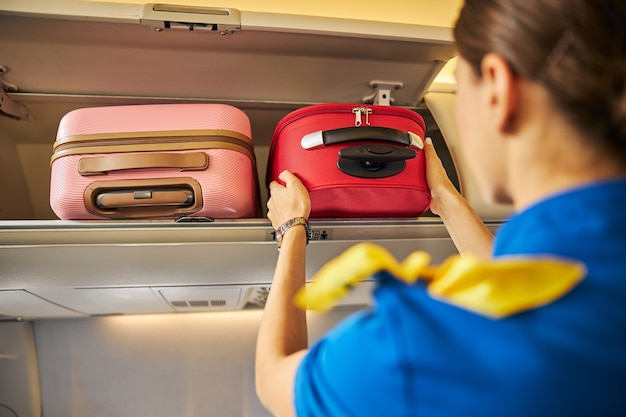 Stewardess putting a suitcase into an overhead compartment