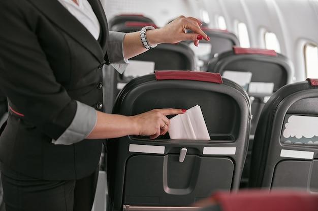 スチュワーデスは飛行機のジェット機の座席にナプキンを突き刺した。現代の飛行機の客室のインテリア。トリミング画像の女性は制服を着ています。民間商用航空。空の旅のコンセプト
