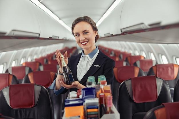飛行機のジェット機の客室にアルコールが入ったスチュワーデスショーボトル。モダンな飛行機のインテリア。笑顔のヨーロッパの女性は制服を着てカメラを見ています。民間商用航空。空の旅のコンセプト