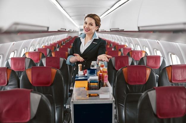 飛行機のジェット機の客室でフードトロリーを見せているスチュワーデス。モダンな飛行機のインテリア。笑顔のヨーロッパの女性は制服を着てカメラを見ています。民間商用航空。空の旅のコンセプト