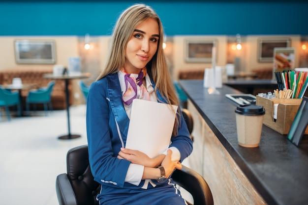 Стюардесса сидит за барной стойкой в кафе аэропорта