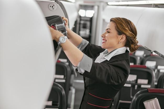 スチュワーデスは飛行機のジェット機の客室の棚から荷物を受け取ります。モダンな飛行機のインテリア。笑顔のヨーロッパの女性は制服を着ています。民間商用航空。空の旅のコンセプト