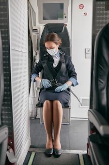Стюардесса пристегивается ремнем безопасности пассажирского самолета. интерьер современного самолета. кавказская женщина носит униформу, латексные перчатки и медицинскую маску. гражданская коммерческая авиация. концепция путешествия по воздуху