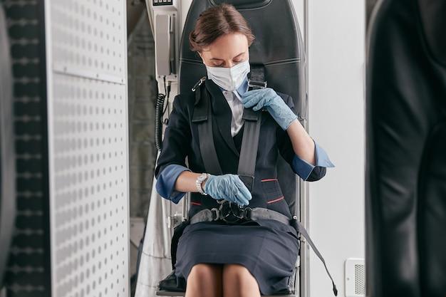 Стюардесса пристегивается ремнем безопасности пассажирского самолета. интерьер современного самолета. европейские женщины носят униформу, латексные перчатки и медицинскую маску. гражданская коммерческая авиация. концепция путешествия по воздуху