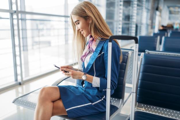 Стюардесса по телефону в зоне ожидания в аэропорту