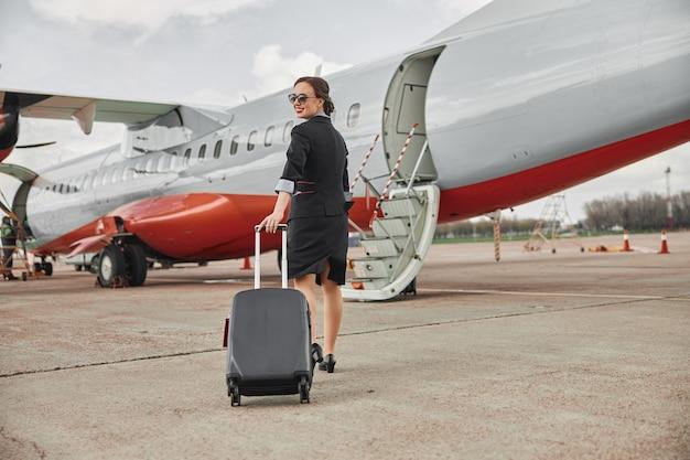 スチュワーデスは飛行機のジェット機への滑走路で荷物を持って歩きます。はしご付きの現代の旅客機。笑顔の若い女性の背面図は、制服と眼鏡を着用します。民間商用航空。空の旅のコンセプト