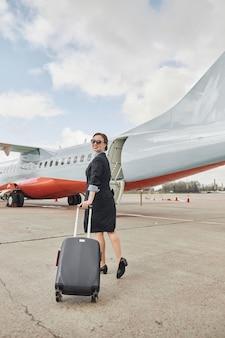 飛行機のジェット機の近くの滑走路を荷物を持って歩くスチュワーデス。はしご付きの現代の旅客機。笑顔の若い女性は制服と眼鏡を着用します。民間商用航空。空の旅のコンセプト