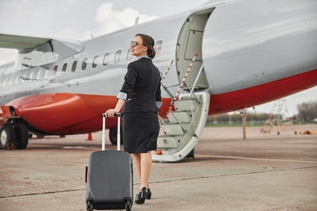 飛行機のジェット機への滑走路で荷物を持って歩くスチュワーデス。はしご付きの現代の旅客機。笑顔の女性の背面図は、制服と眼鏡を着用します。民間商用航空。空の旅のコンセプト