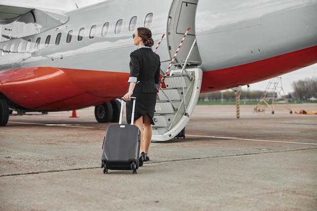 飛行機のジェット機への滑走路で荷物を持って歩くスチュワーデス。はしご付きの現代の旅客機。若い女性の背面図は、制服と眼鏡を着用します。民間商用航空。空の旅のコンセプト
