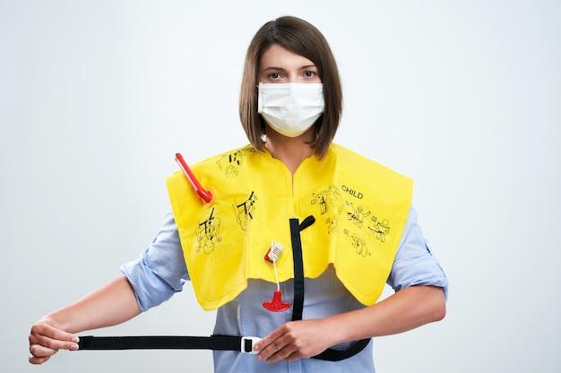 保護マスクを着用し、白い背景の上に分離された航空機のルールを説明するスチュワーデス