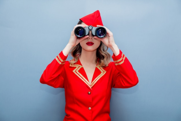 Stewardess wearing in red uniform with binoculars