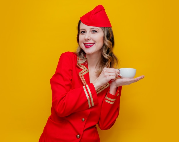 Stewardess wearing in red uniform with cup of coffee or tea