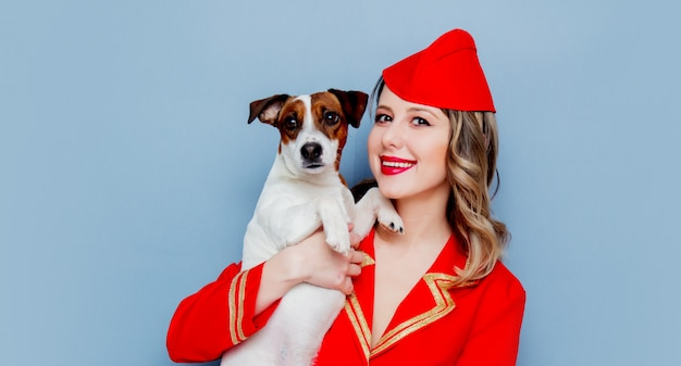 Stewardess wearing in red uniform with dog