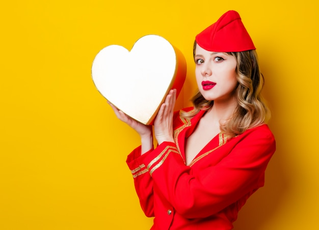 Stewardess wearing in red uniform with heart shape holiday gfit box