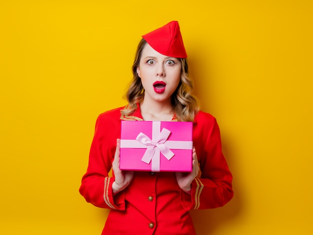 Stewardess wearing in red uniform with holiday gfit box