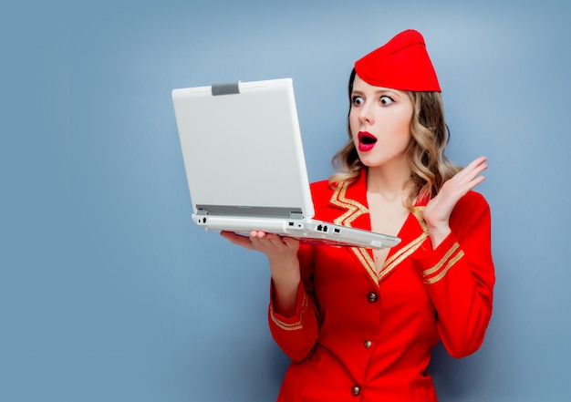 Stewardess wearing in red uniform with laptop computer