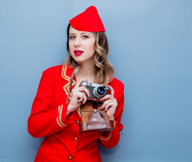 Stewardess wearing in red uniform with vintage camera