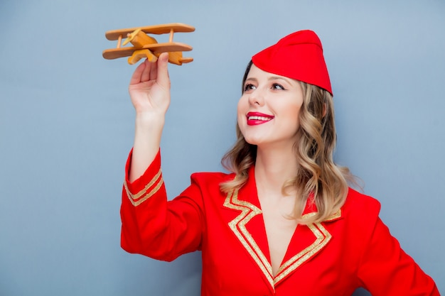 Stewardess wearing in red uniform with wooden airplane