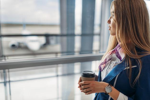 Стюардесса с кофе на сиденье в зоне ожидания