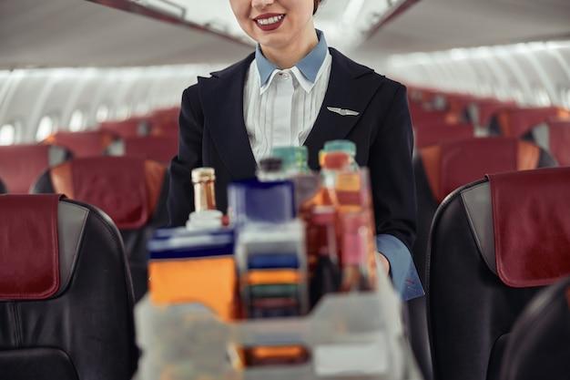 飛行機のジェット機の客室にフードトロリーを持ったスチュワーデス。モダンな飛行機のインテリア。制服を着た女性のトリミング画像。民間商用航空。空の旅のコンセプト