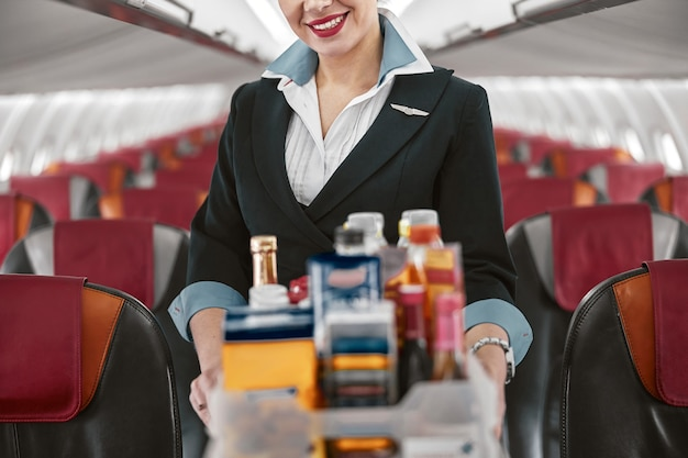 飛行機のジェット機の客室にフードトロリーを持ったスチュワーデス。モダンな飛行機のインテリア。制服を着た女性の部分画像。民間商用航空。空の旅のコンセプト