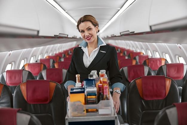 飛行機のジェット機の客室にフードトロリーを持ったスチュワーデス。モダンな飛行機のインテリア。笑顔のヨーロッパの女性は制服を着てカメラを見ています。民間商用航空。空の旅のコンセプト