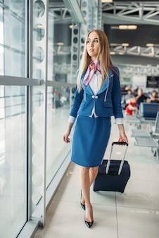 Стюардесса с чемоданом в зале ожидания аэропорта