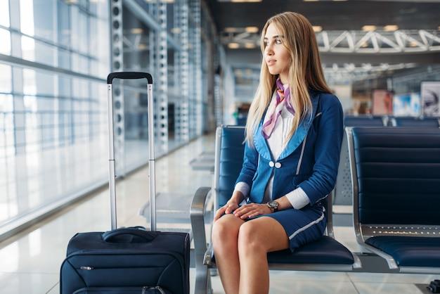 Стюардесса с чемоданом сидит в зоне ожидания