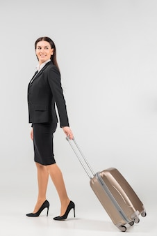 Stewardess with suitcase turning round