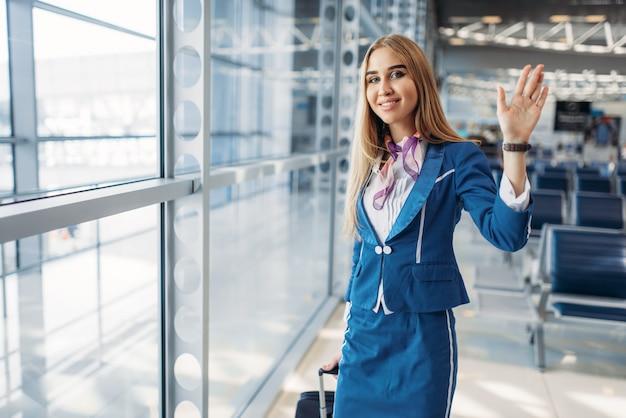 Стюардесса с чемоданом машет руками в аэропорту
