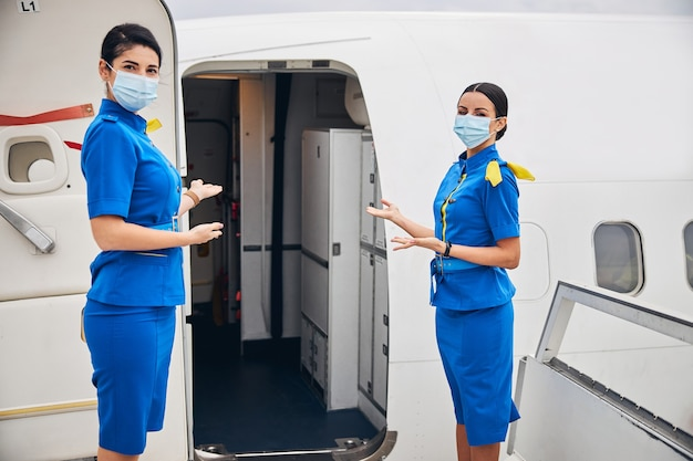 Stewardesses in face masks inviting passengers aboard