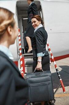 はしごを上って飛行機のジェット機に向かうスチュワーデス。現代の旅客機。手荷物のある女性は制服を着ています。チームワーク。晴れた日中。民間商用航空。空の旅のコンセプト