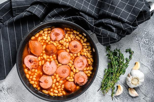 鍋にスモークソーセージとトマトソースを入れた豆の煮込み