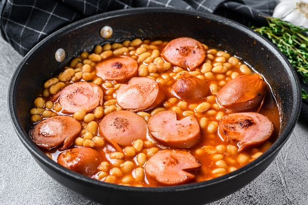 Stewed beans with smoked sausage and tomato sauce in a pan.   top view.