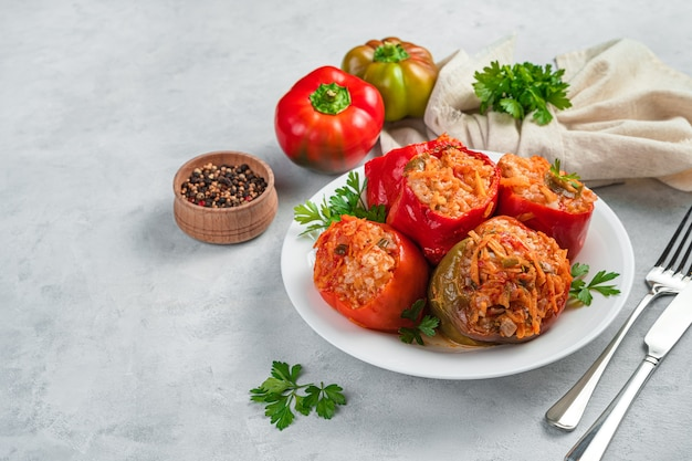 Stewed bell pepper stuffed with meat and rice in a white plate on a gray background