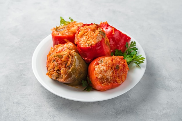 Stewed bell pepper stuffed with turkey and rice on a gray background