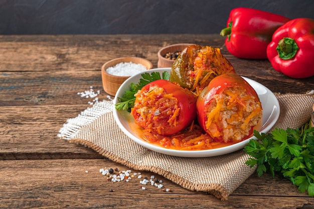 Stewed bell pepper with meat and rice on a wooden background