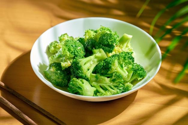 Тушеная брокколи в чесночном соусе в белой тарелке. китайский рецепт и кухня