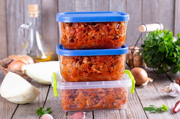 Stewed cabbage in a container on a wooden background for freezing. frozen food, healthy food