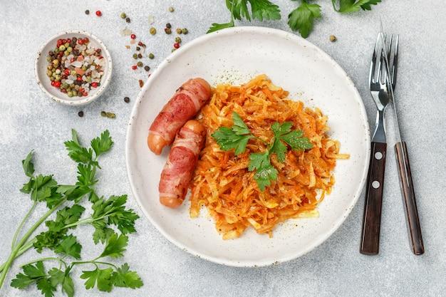 Капуста тушеная с морковью, луком и помидорами и колбасками в беконе с петрушкой и специями