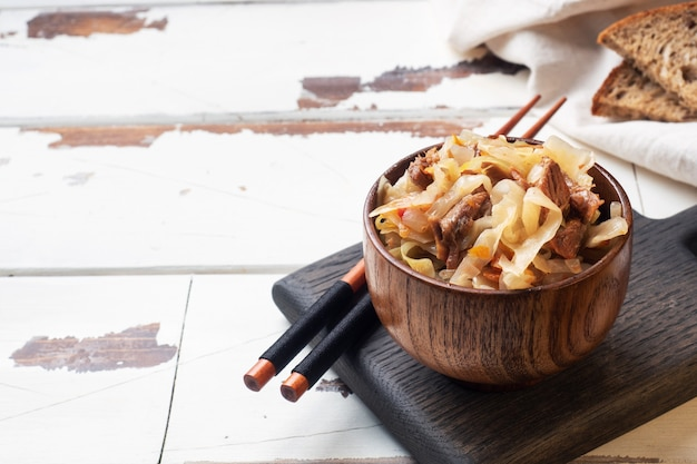 Stewed cabbage with meat in a wooden bowl on a wooden background. traditional russian dish of solyanka. copy space